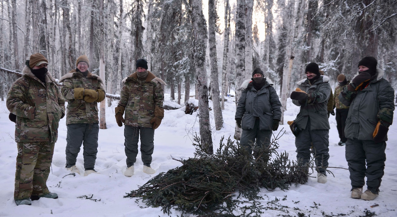 military members standing around a pile of pine branches in snow