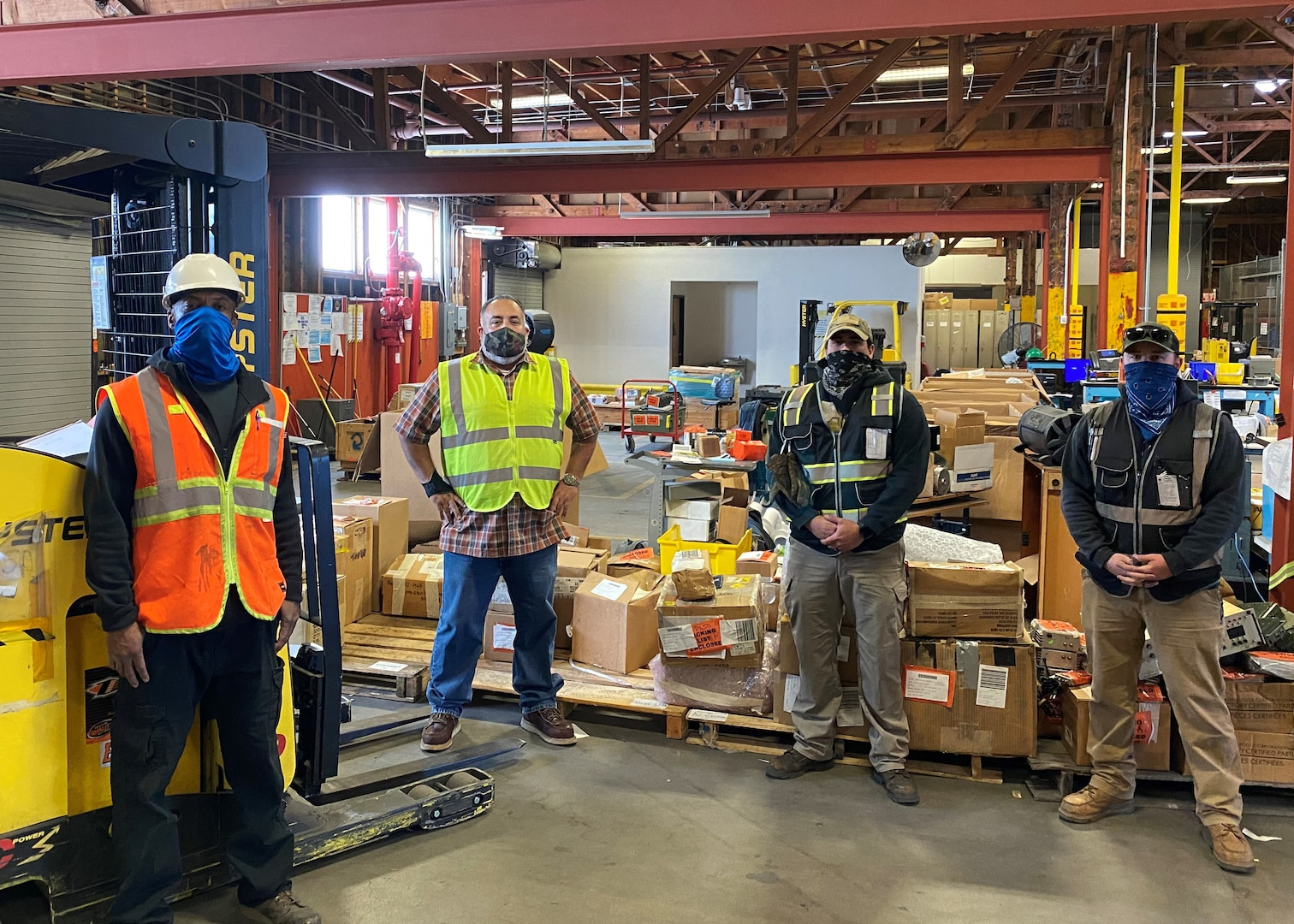Four men wearing personal protective equipment for warehouse work and facemask stand socially distanced inside a warehouse with a forklift and boxes on pallets around them.