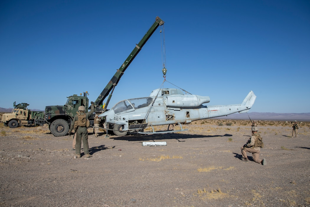 Marines providing security while lifting aircraft with model crane so that it can be repaired.