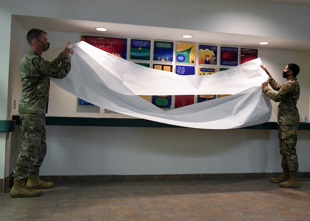 two military members removing the covering from a display