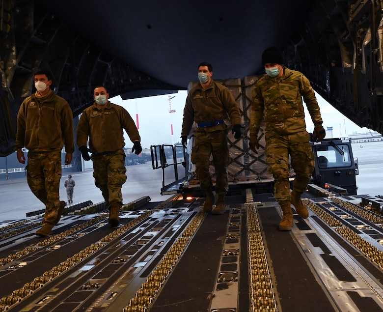 Airmen from the 721st Aerial Port Squadron walk into a C-17 Globemaster III aircraft to retrieve a pallet at Ramstein Air Base, Germany, Feb. 2, 2021. The Defense Logistics Agency requested a shipment of more than 400,000 masks to ensure U.S. forces in Germany are compliant with host nation requirements. The 721st APS plays an important role in the distribution of masks and other COVID-19 protective equipment... (U.S. Air Force photo by Senior Airman Thomas Karol)