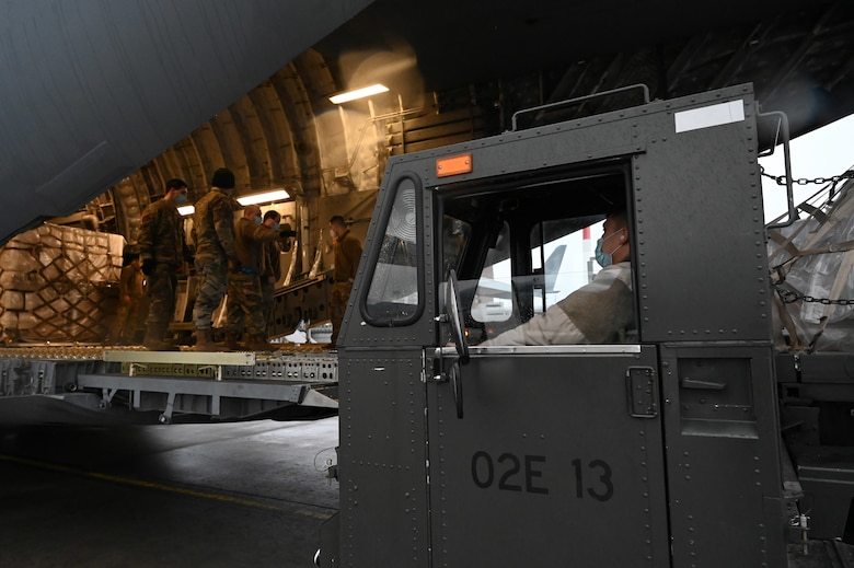 U.S. Air Force Airman 1st Class Kevin Sunti, 721st Aerial Port Squadron ramp services specialist, operates a Tunner aircraft loader at Ramstein Air Base, Germany, Feb. 2, 2021. Approximately 15 tons of masks were delivered to Ramstein by the Defense Logistics Agency. The 721st APS plays an important role in the distribution of masks and other COVID-19 protective equipment. (U.S. Air Force photo by Senior Airman Thomas Karol)