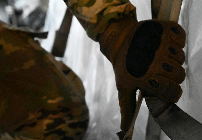 U.S. Air Force Airman David Hanus, 721st Aerial Port Squadron ramp services specialist, checks a strap at Ramstein Air Base, Germany, Feb. 2, 2021. Hanus and other 721st APS Airmen unloaded approximately 400,000 masks for U.S. service members in Germany. The masks, which are more effective than cloth face coverings, help service members remain compliant with host nation regulations and contribute to the joint fight against COVID-19.  The 721st APS plays an important role in the distribution of masks and other COVID-19 protective equipment.. (U.S. Air Force photo by Senior Airman Thomas Karol)