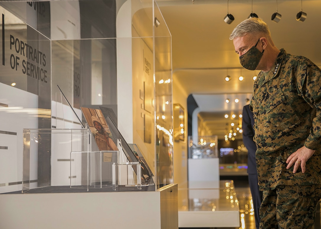 """U.S. Marine Corps Gen. Kenneth F. McKenzie, Jr., the commander of U.S. Central Command, views a piece of the """"MacDill Air Force Base at Home and Abroad"""" art display at Tampa International Airport, Fl., Feb. 1, 2021. The new exhibit is a collection of commissioned artwork and photos depicting the various branches of the military and the lives of those who serve in Southwest Asia. (U.S. Marine Corps photo by Sgt. Roderick Jacquote)"""
