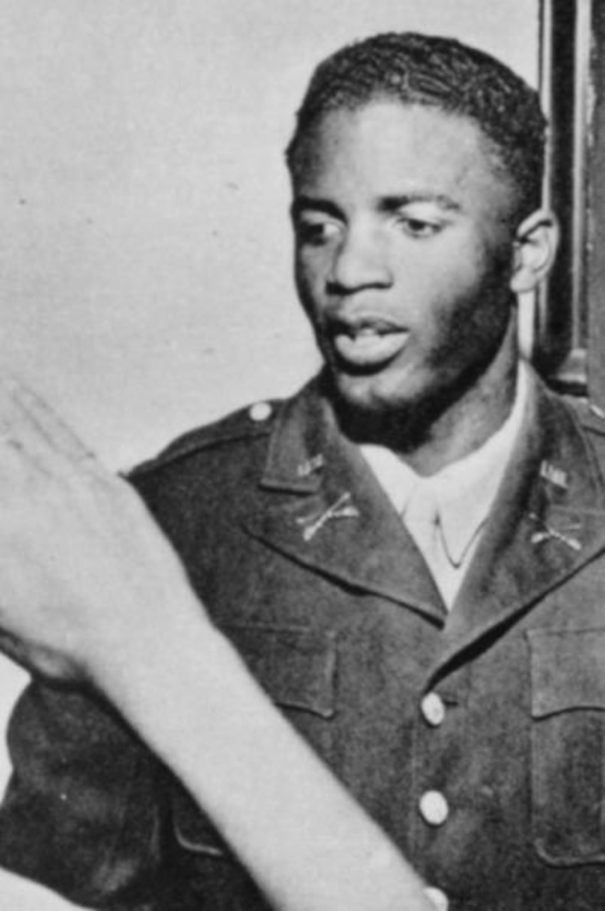 A young man is dressed in a military uniform; the arm of someone saluting is seen in the foreground.