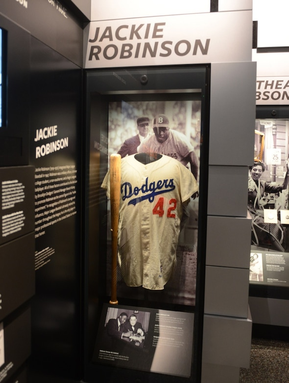 A No. 42 baseball jersey with the name Dodgers splashed across the front is on display in a museum case.