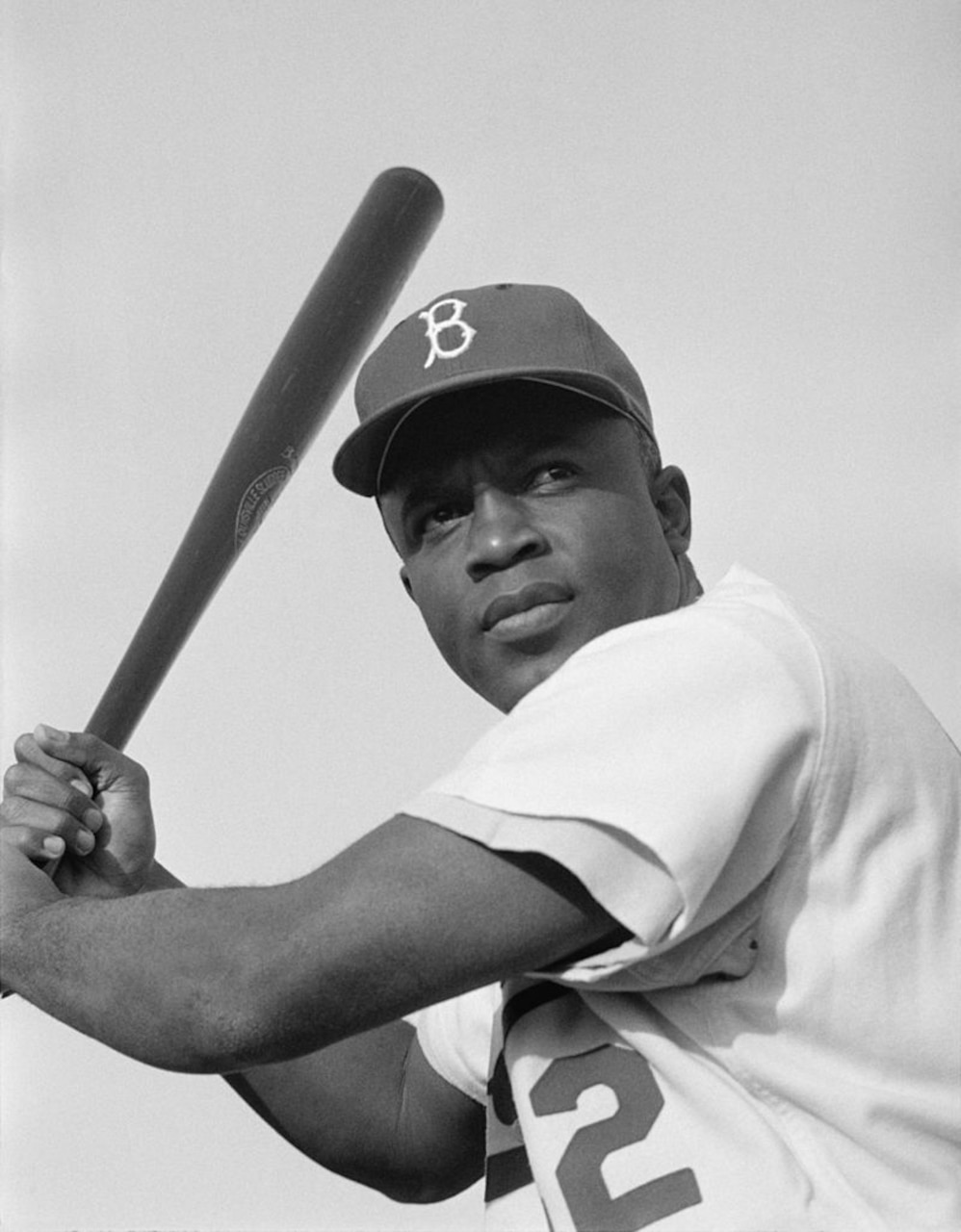 A baseball player, holding a bat, poses for a photo.