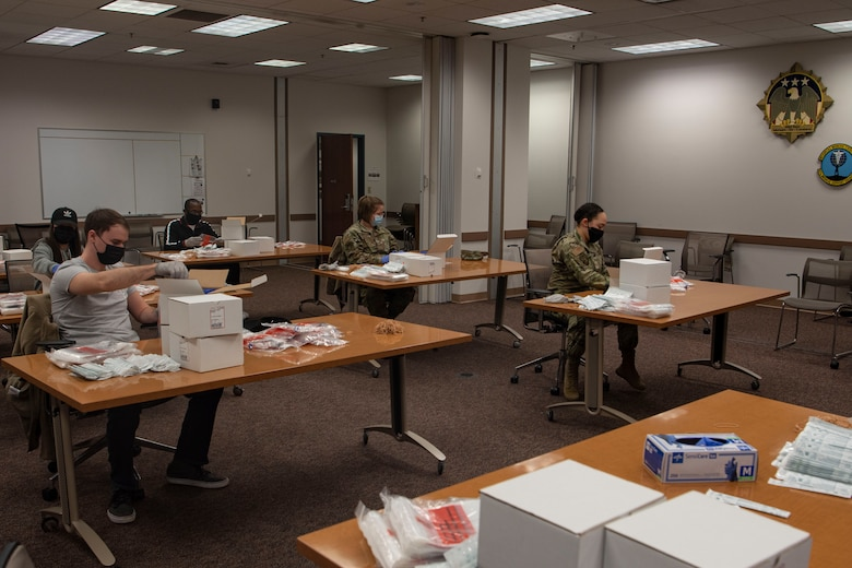 Photo of volunteers putting together COVID-19 test kits.
