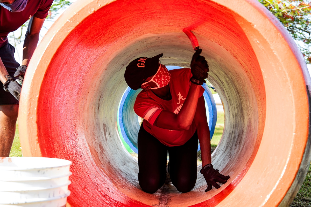 An airman in civilian clothes paints the inside of a tunnel pinkish-red.