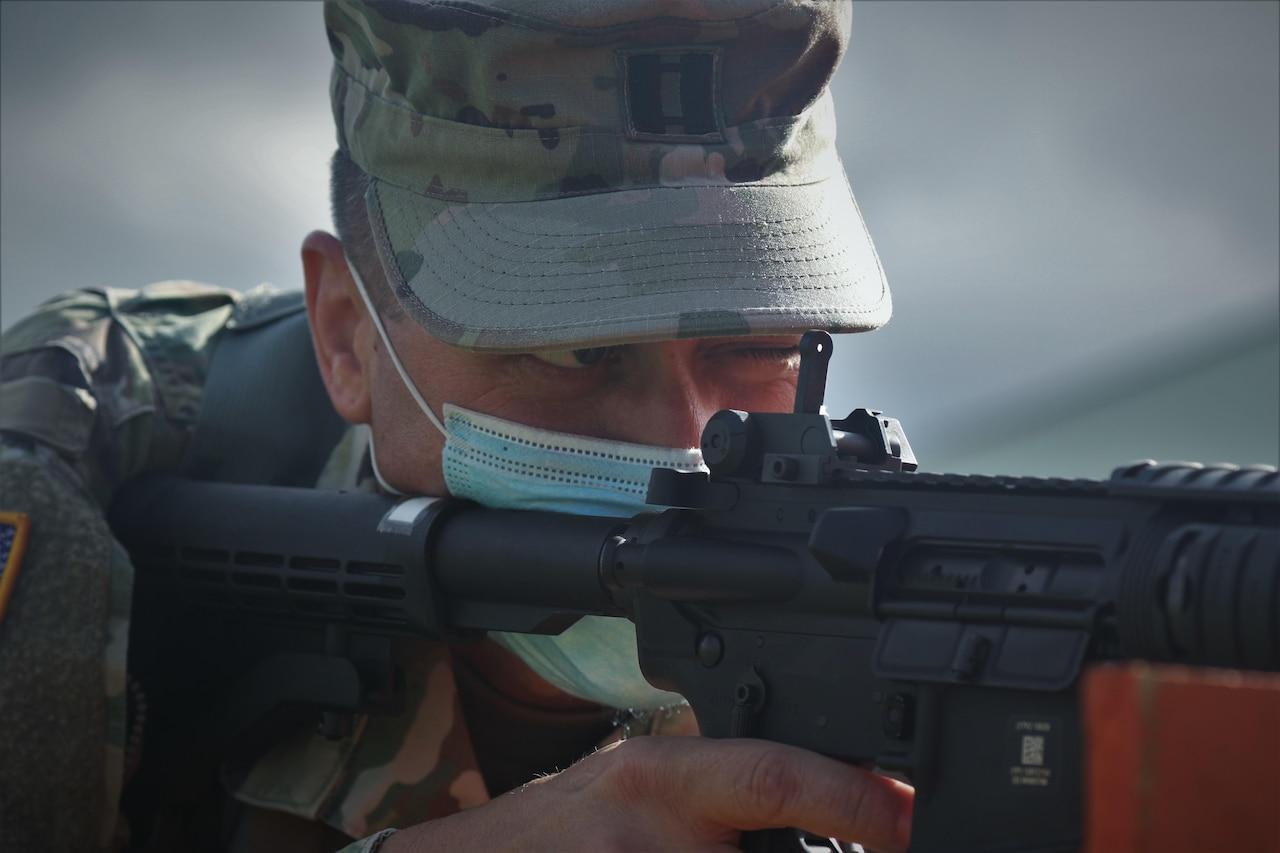 A man in uniform aims a weapon.