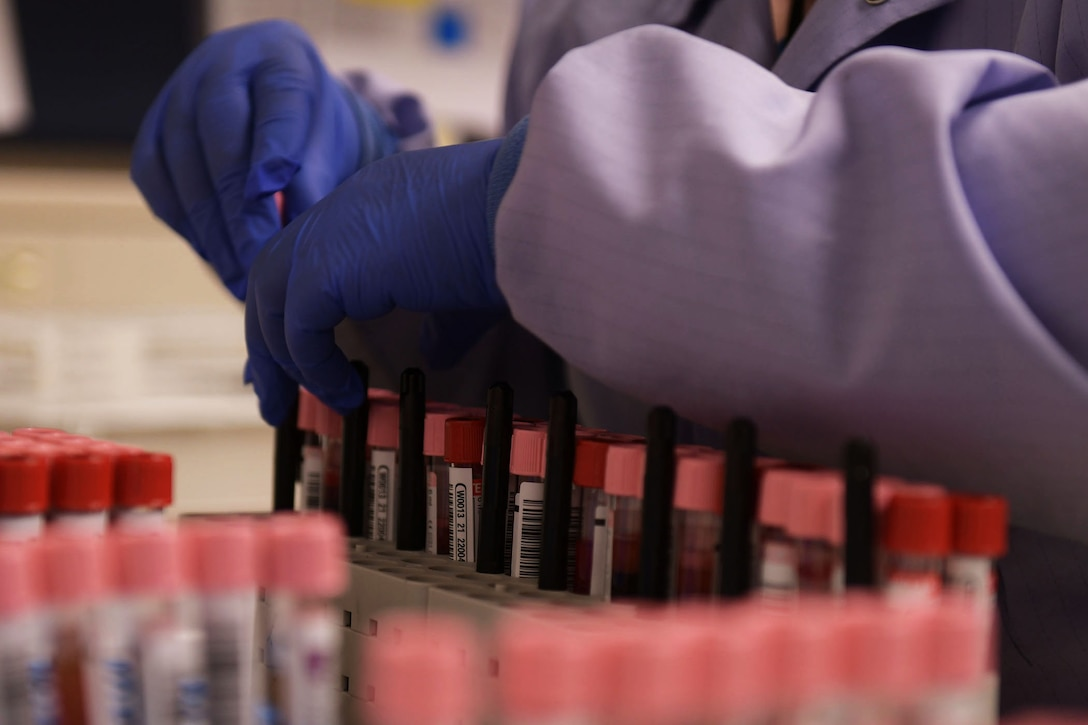 A laboratory technician wearing gloves organizes vials of blood.