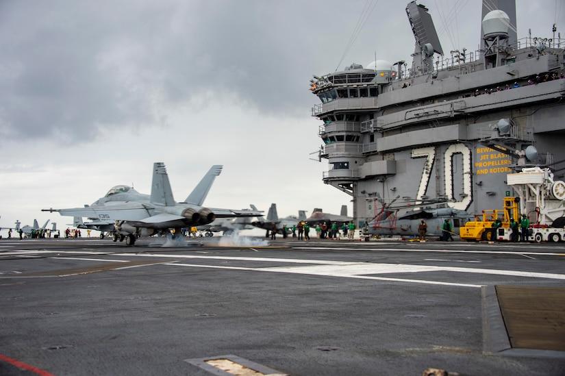 A jet lands on an aircraft carrier.