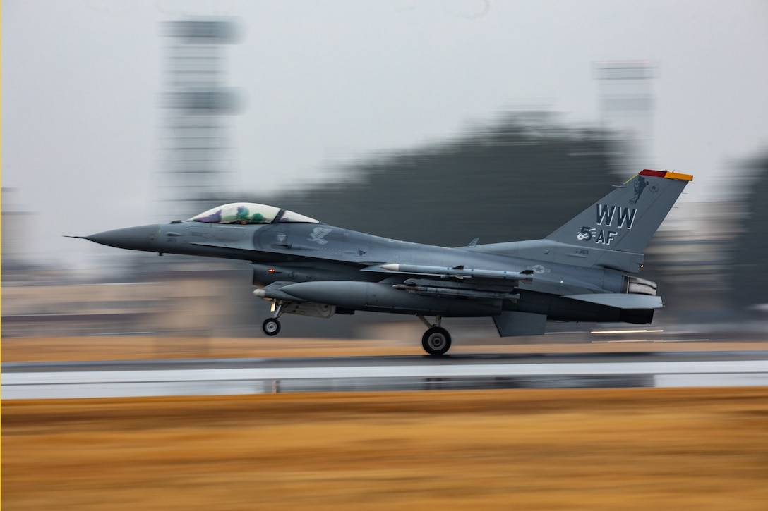 An F-16 takes off the flightline. The background is blurry and the photos are clear.