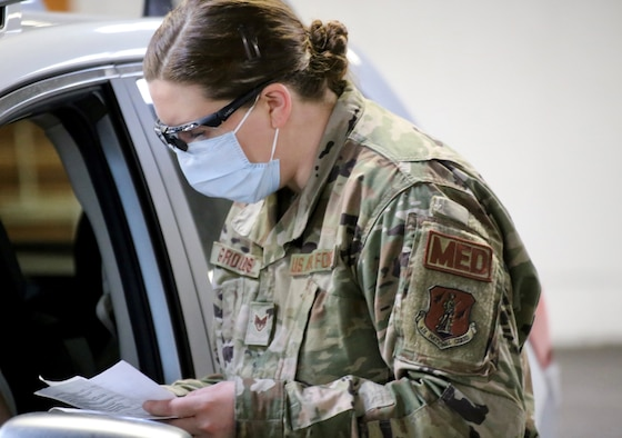 Staff Sgt. Melinda Grounds, a medic with the 141st Medical Group and a registered nurse in Idaho, goes through a questionnaire with a visitor to the mass vaccination site at the Clark County Fairgrounds in Ridgefield, Wash., Jan. 28, 2021. The Washington National Guard is helping at four vaccination sites.