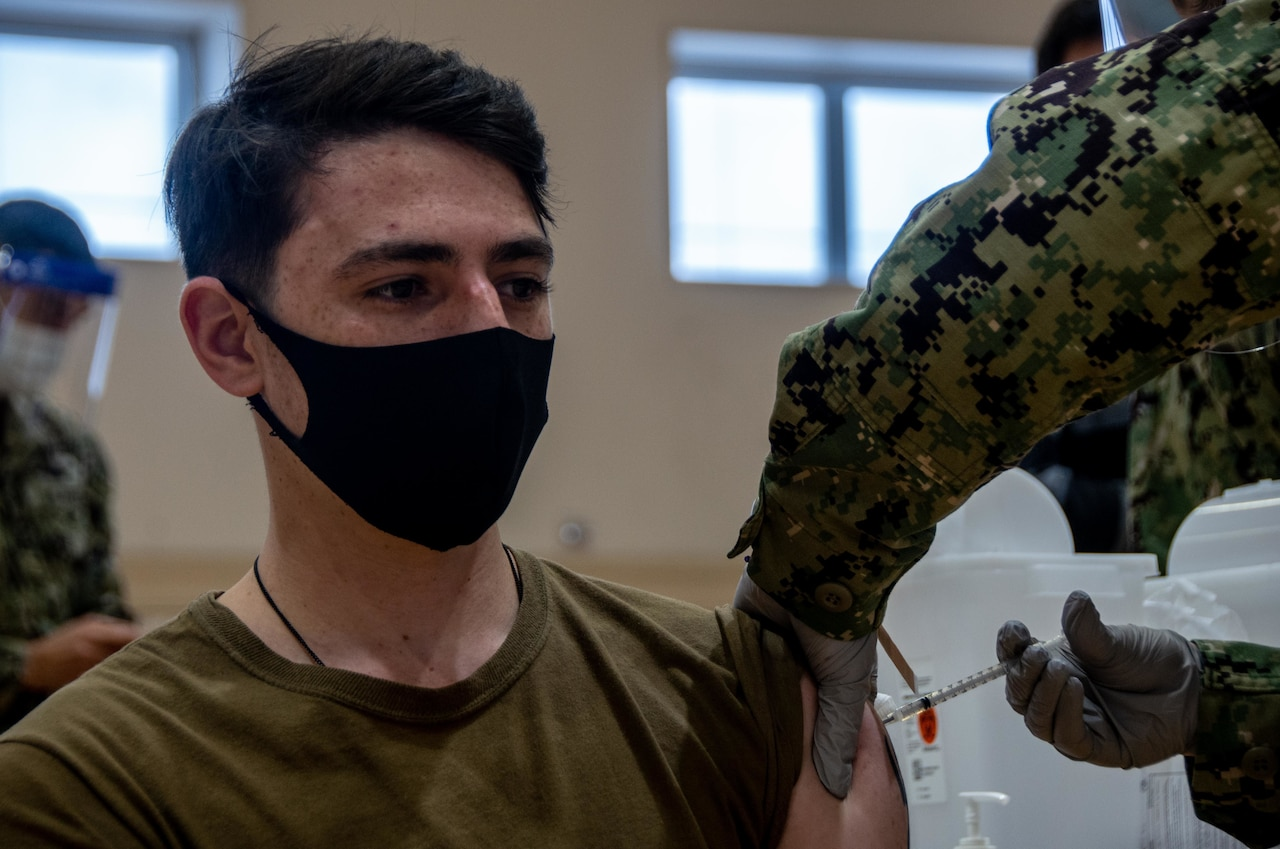 A sailor wearing a protective face mask receives a vaccine shot.