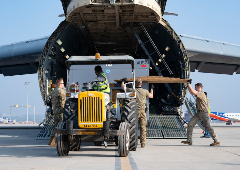34th Expeditionary Bomb Squadron Airmen from Ellsworth Air Force Base, S.D., work alongside Indian airfield operations specialists to unload B-1B Lancer maintenance equipment from a C-5M Super Galaxy at Kempegowda International Airport in Bengaluru, India, Feb. 1, 2021. The 34th EBS is in India to support the B-1's participation in Aero India 2021. Aero India provides the opportunity to build a stronger relationship between the United States and India, as well as with the international community. (U.S. Air Force photo by Senior Airman Christina Bennett)