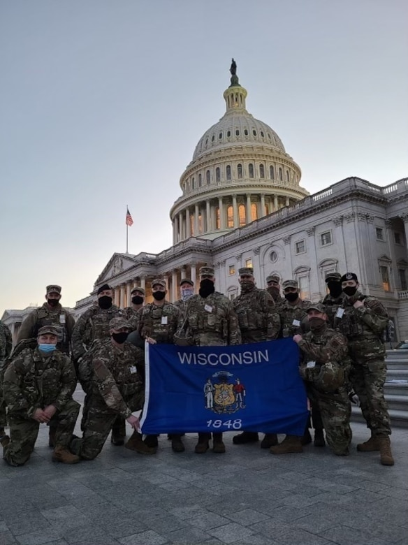 Members from the 128th Air Refueling Wing stand with the Wisconsin state flag on the steps of the U.S. Capitol building Jan. 20, 2021. In the days leading up to the 59th presidential inauguration more than 125 Wisconsin Airmen from the 128th Air Refueling Wing, 115th Fighter Wing and Volk Field Combat Readiness Training Center mobilized to Washington D.C. to assist with security efforts for the event. (Courtesy photo)