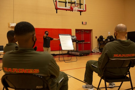 Mr. Allen Sese, the High Intensity Tactical Training (HITT) Coordinator for U.S. Marine Corps Forces Command, Headquarters and Service Battalion, explains to the students the plane of motion for a workout during a HITT course in the Hopkins Gymnasium on Camp Elmore, Norfolk, Virginia, January 26, 2021. HITT is a comprehensive strength and conditioning program that focuses on maintaining and improving physical resiliency and combat readiness. The Marines that progressed through the course will be a knowledgeable resource for physical training (PT) and will be able to conduct PT properly within their respective units. (U.S. Marine Corps Photo by Lance Cpl. Jack Chen/released)