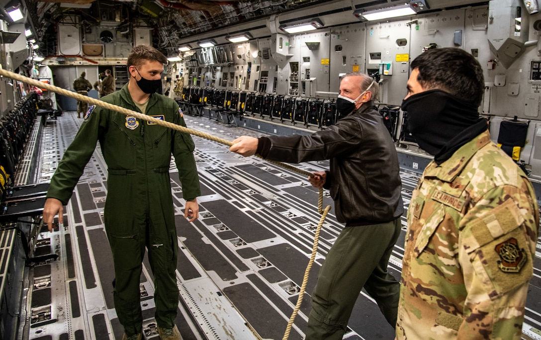 Col. John Rockwell, 436th Medical Group aerospace medicine chief, tests an emergency egress rope with Staff Sgt. Craig Tocci, 3rd Airlift Squadron loadmaster, and Technical Sgt. Jose Cardoza, 3rd AS loadmaster, on a C-17 Globemaster III at Dover Air Force Base, Delaware, Jan. 28, 2021. Emergency egress is a training requirement for all aircrew members. The 3rd AS routinely trains to support global engagement through direct delivery of time-critical theater deployment assets and ensure aircrew operational readiness. (U.S. Air Force photo by Airman 1st Class Faith Schaefer)