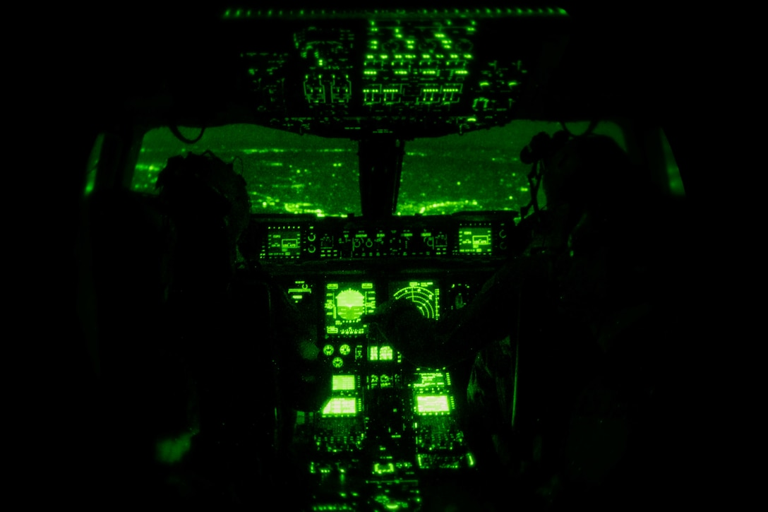 1st Lt. Zachary Pruitt, 3rd Airlift Squadron pilot, and Capt. Corey Landis, 3rd AS instructor pilot, fly a C-17 Globemaster III over Pennsylvania, while wearing night vision goggles, Jan. 28, 2021. In combat, flying at night without artificial light minimizes visibility of the aircraft and reduces threat from potential enemies. The 3rd AS routinely trains to support global engagement through direct delivery of time-critical theater deployment assets and ensure aircrew operational readiness. (U.S. Air Force photo by Airman 1st Class Faith Schaefer)
