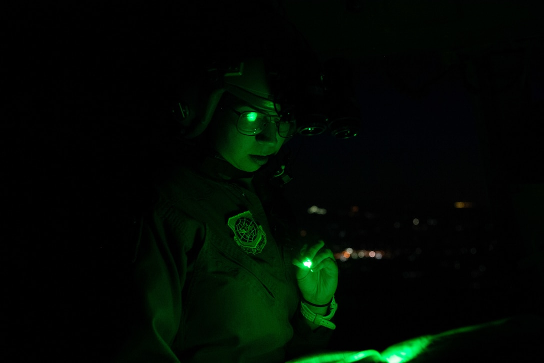 Capt. Sarah Aravich, 3rd Airlift Squadron pilot, reads a map during a training sortie on a C-17 Globemaster III over Pennsylvania, Jan. 28, 2021. In combat, flying at night without artificial light minimizes visibility of the aircraft and reduces threat from potential enemies. The 3rd AS routinely trains to support global engagement through direct delivery of time-critical theater deployment assets and ensure aircrew operational readiness. (U.S. Air Force photo by Airman 1st Class Faith Schaefer)