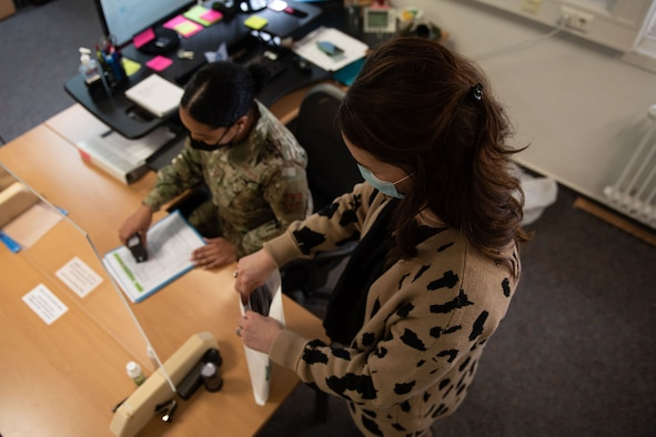 U.S. Air Force Staff Sgt. Valerie Gutierrez (left) and Danielle Smith, both 52nd MPF passport acceptance agents, work on passport paperwork, Feb. 3, 2021, at Spangdahlem Air Base, Germany. Despite the challenges of COVID-19, the MPF is still working to meet the needs of service members, even if that means they must make adjustments to their standard procedures. (U.S. Air Force photo by Senior Airman Melody W. Howley)