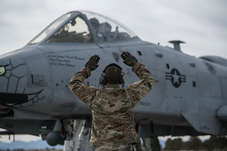A U.S. Airman with the Indiana Air National Guard, assigned to the 122nd Fighter Wing, Fort Wayne, Indiana, signals an A-10C Thunderbolt II pilot before flight at Red Flag 21-1, Nellis Air Force Base, Nevada, Jan. 23, 2021. The event, held several times per year, is a U.S. Air Force premier air-to-air combat training exercise. (U.S. Air National Guard photo by Staff Sgt. Justin Andras)