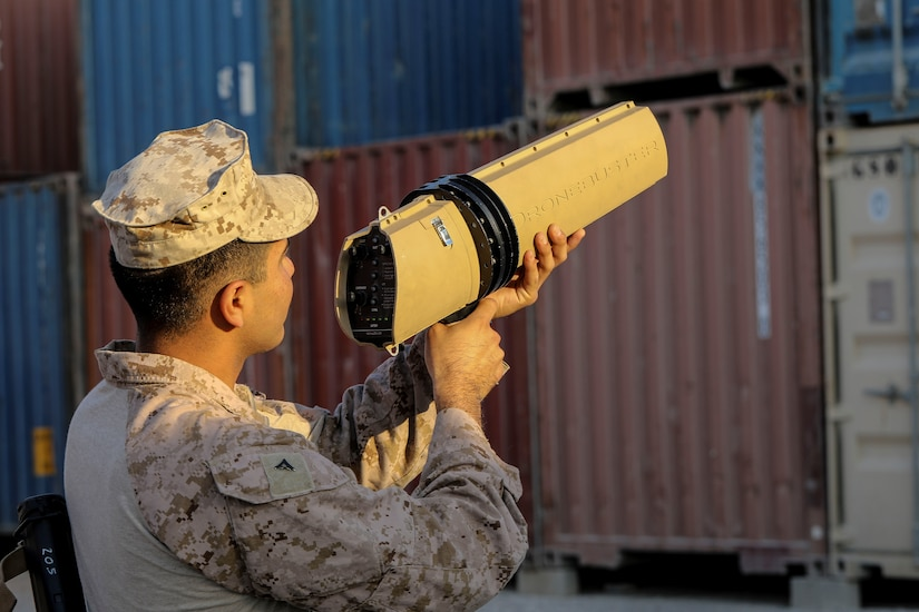 A service member points a large gun-like device into the air.