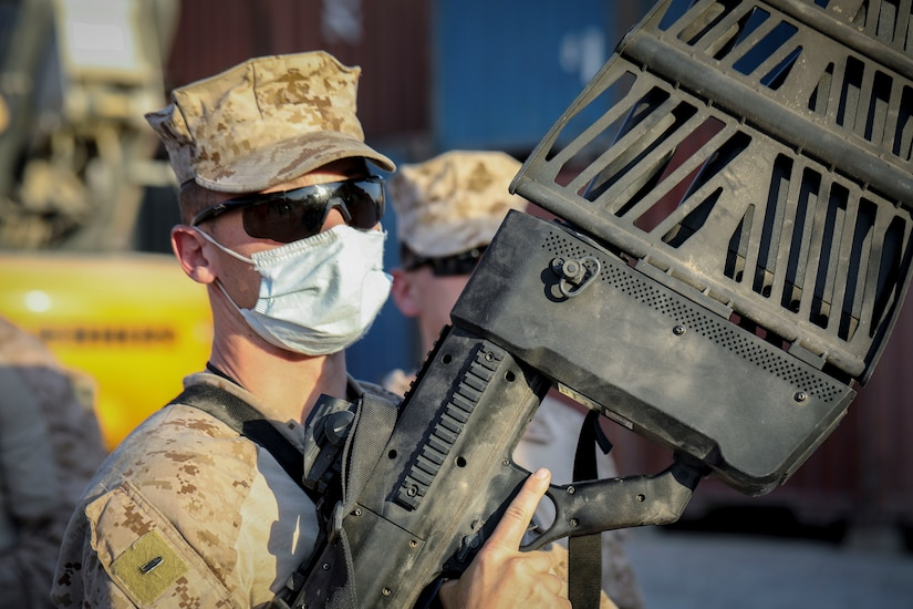 A service member holds a large gun-like device.
