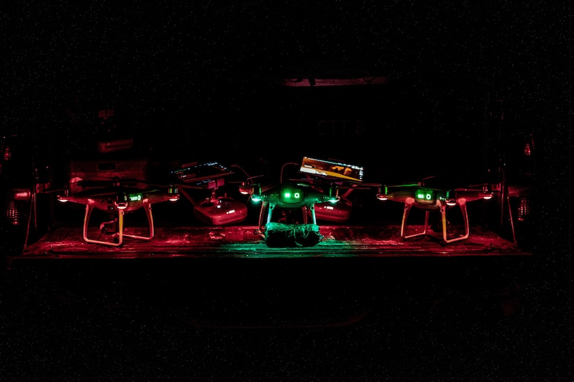Several drones sitting on the ground light up at night.