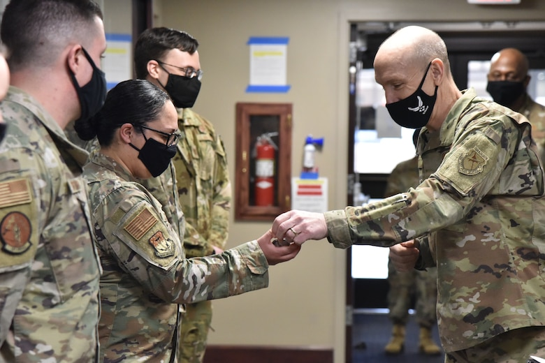Air Force Vice Chief of Staff Gen. David Allvin presents a coin for exceptional performance to Tech Sgt. Mayra Corona, 341st Medical Group Military Health System Genesis project coordinator, Jan. 29, 2021, during a trip to Malmstrom Air Force Base, Mont. (U.S. Air Force photo by Senior Airman Daniel Brosam)
