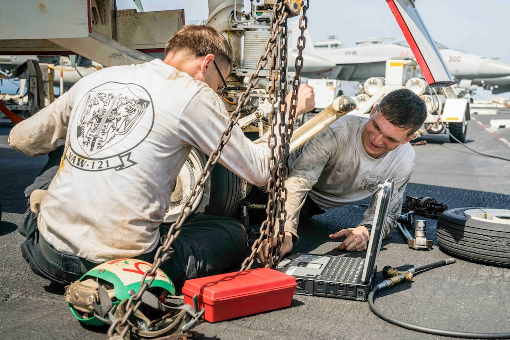 """Aviation Structural Mechanic 3rd Class Joseph Leroy (left), and Aviation Structural Mechanic Airman James Baker change the nose landing gear tire of an E-2D Hawkeye from the """"Bluetails"""" of Carrier Airborne Early Warning Squadron (VAW) 121 on the flight deck of the aircraft carrier USS Abraham Lincoln (CVN 72)."""