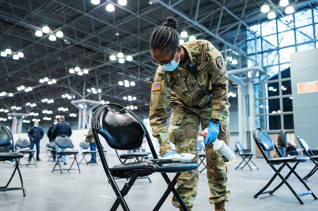 A soldier wearing a face mask and gloves wipes the seat of a chair with a cloth. In her other hand, she holds a spray bottle.