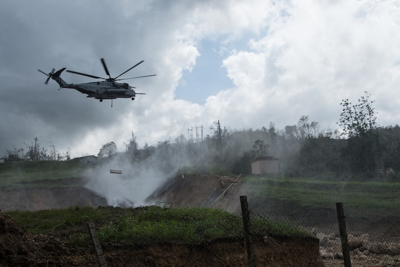A U.S. Marine Corps CH53, Sikorsky Sea Stallion heavy-lift transport helicopter, lifts five-ton Jersey barriers into the Guajataca Dam, in Guajataca, PuertoRico, Monday. USACE is assisting the Puerto Rico Electric Power Authority in efforts to reduce the risk from Guajataca Dam to downstream communities by performing structural assessments, and planning and coordinating aircraft, equipment and materials to temporarily shore up the damaged spillway. The emergency repairs to the dam is an interagency effort to mitigate damages caused by the heavy rains and inflows from HurricaneMaria. This emergency effort will be followed by a temporary and finally permanent fix in the future.