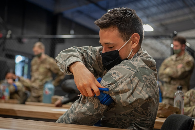 Photo of an Airman practicing applying a tourniquet