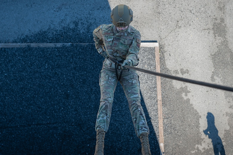 Photo of an Airman rappelling from a tower