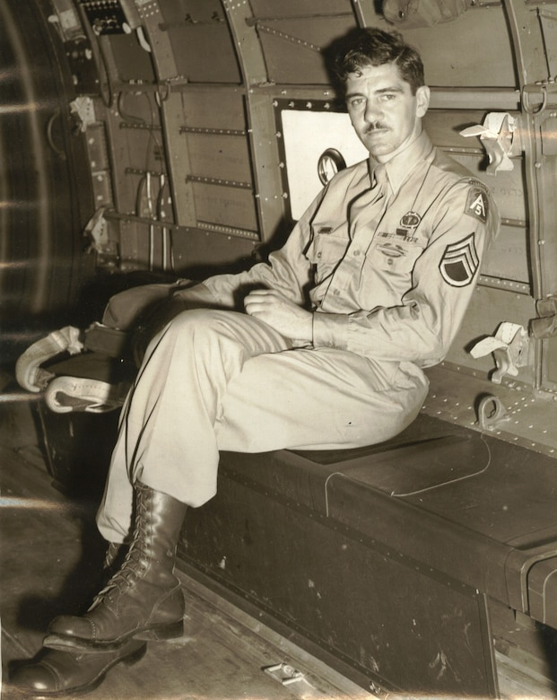 A man with his legs crossed sits in the cargo hold of a plane.
