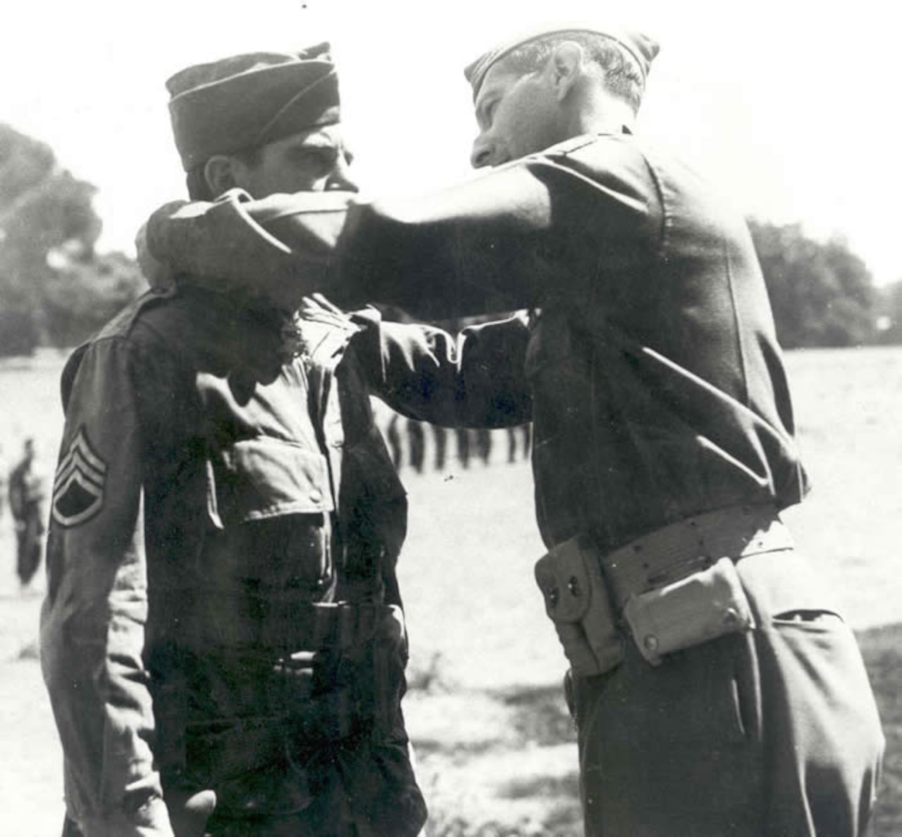 A uniformed man places a medal on a ribbon around the neck of another uniformed man.