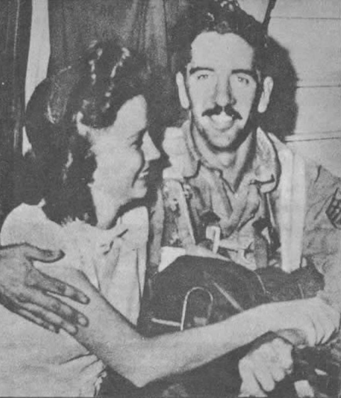 A man sits with his arm around a smiling woman.