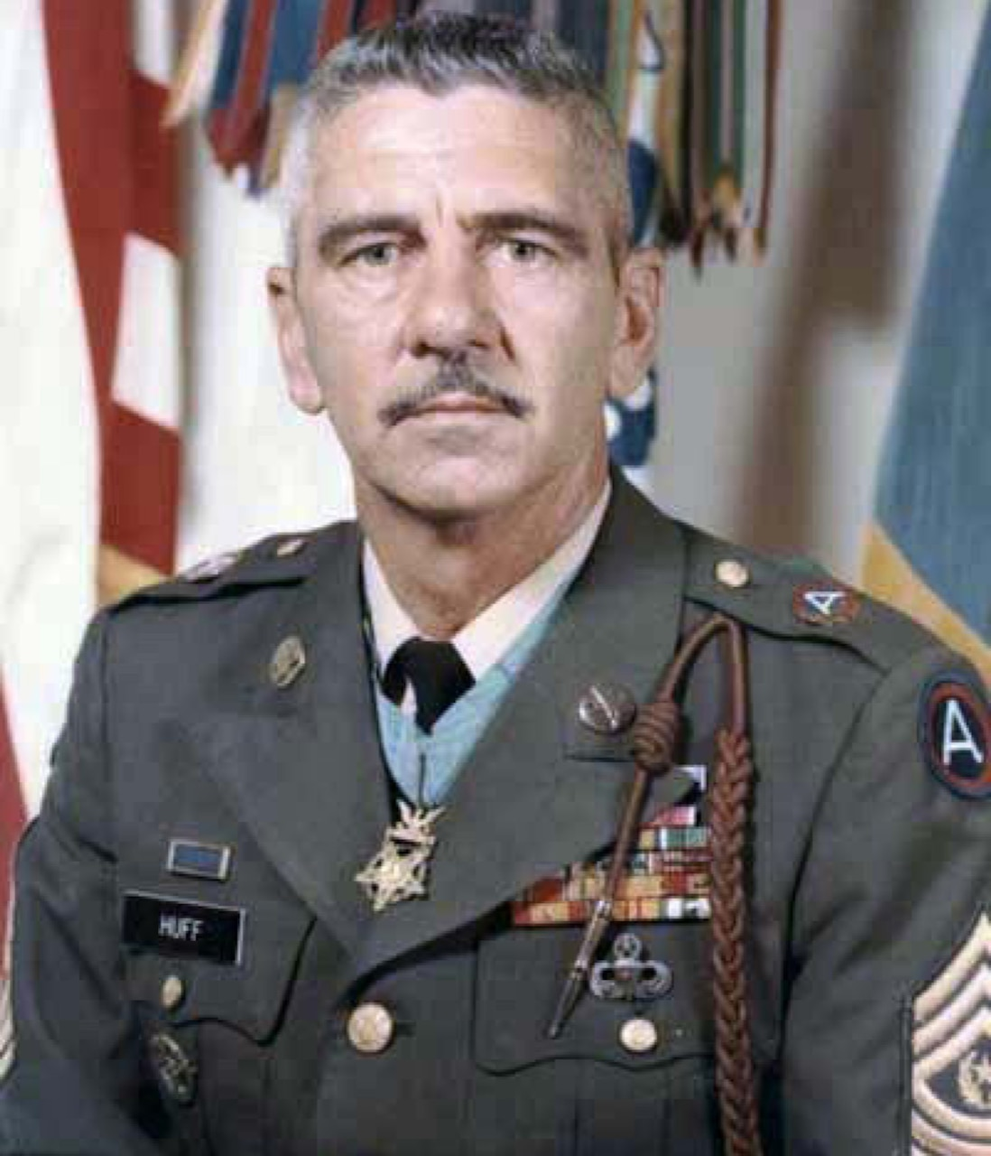 A man in service dress uniform wearing a medal around his neck looks at the camera.