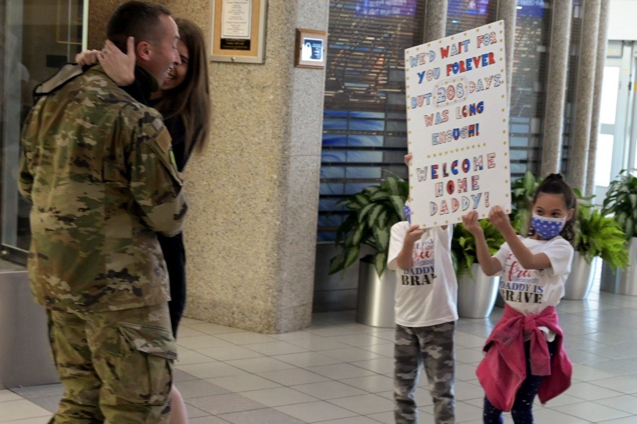An airmen hugs his wife while looking at poster board his children are holding.