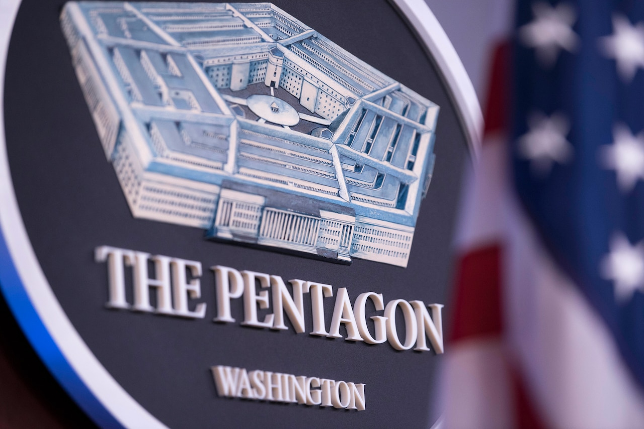 A Pentagon seal hangs on a wall.
