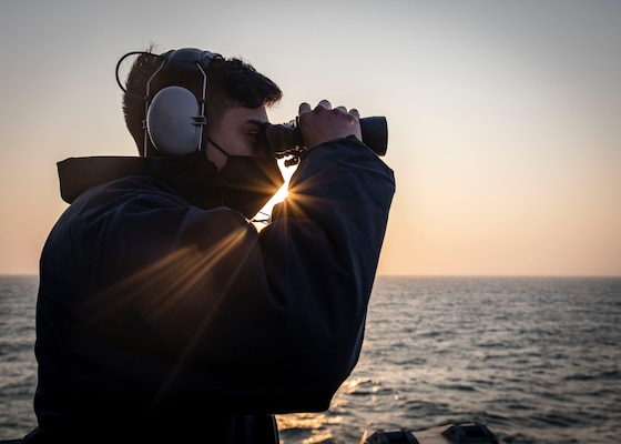 TAIWAN STRAIT - Seaman Frank Medina, from Dallas, Texas, scans the horizon while standing on the bridge wing aboard the Arleigh Burke-class guided-missile destroyer USS John S. McCain (DDG 56) as the ship conducts routine underway operations. McCain is forward-deployed to the U.S. 7th Fleet area of operations in support of security and stability in the Indo-Pacific region.