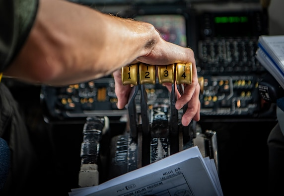 Hand on the throttle of a KC-135 aircraft.