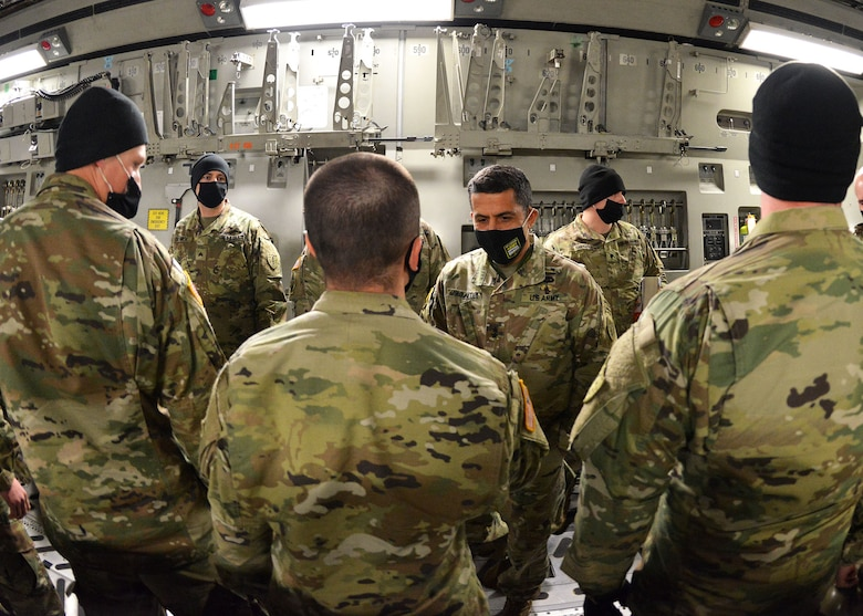 New Hampshire Adjutant Gen. David Mikolaities greets N.H. guardsmen at Pease Air National Guard base aboard a West Virginia National Guard C-17 Globemaster III aircraft upon their return from a week-long mobilization to Washington, D.C. on Jan. 23, 2021.