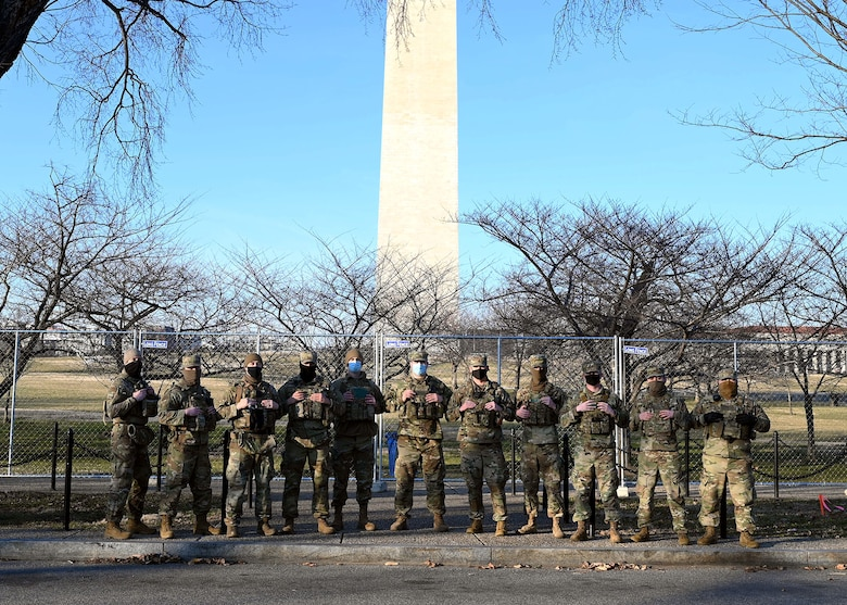Airmen of the 157th Security Forces Squadron, NHANG, pose before the Washington Monument at the National Mall on Jan. 20, 2021, in Washington, D.C.