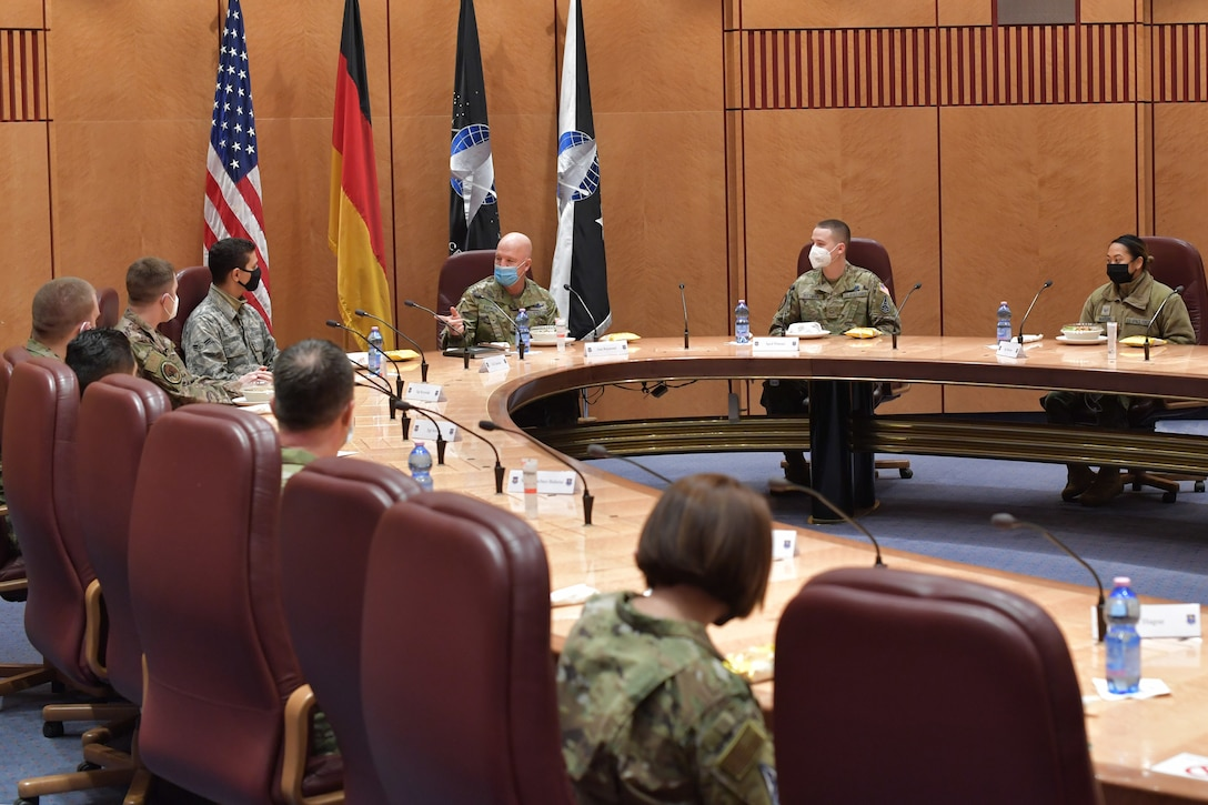 Guardians and Airmen sitting around a conference table.