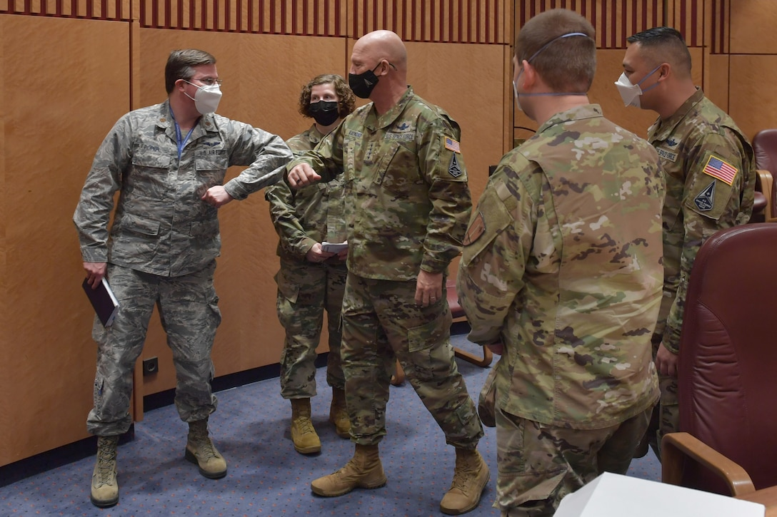Airman bumping elbows with a general.