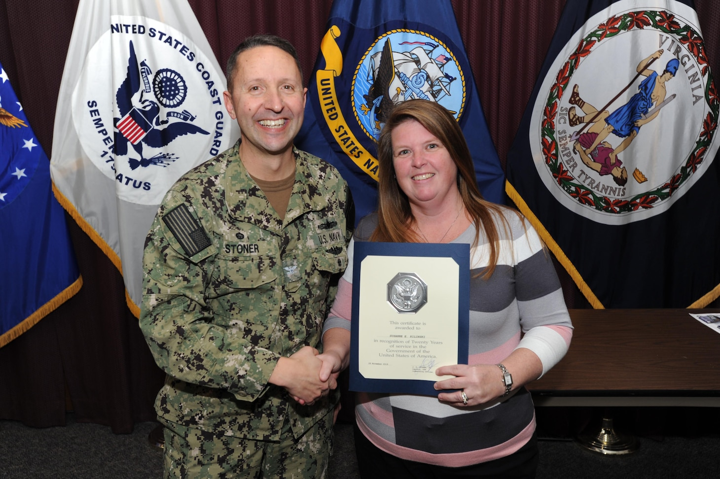 Center for Surface Combat Systems (CSCS) Commanding Officer, Capt. Dave Stoner, recognizes CSCS Financial Management Analyst Mrs. Suzie Kilinski for her 20 years of civilian service at an awards ceremony January 9, 2020.
