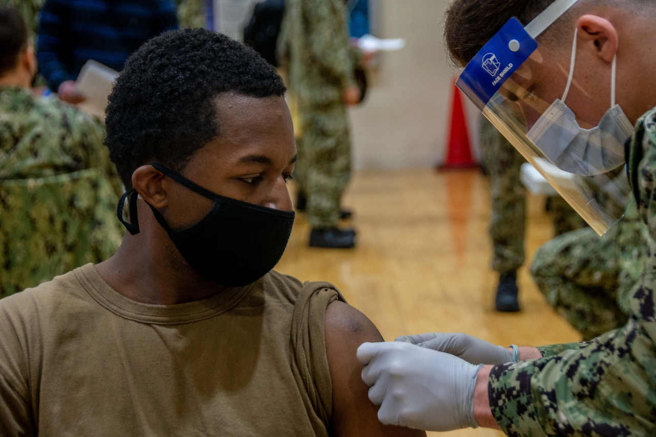 A sailor wearing a protective face mask receives a vaccine shot in the arm.